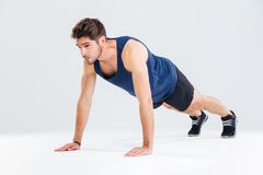 Concentrated young sportsman exercising and doing push ups Stock Photography