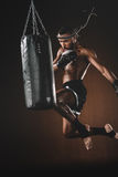 Concentrated young sportsman jumping and thai boxing with punching bag Royalty Free Stock Image
