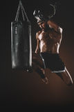 Concentrated young sportsman jumping and thai boxing with punching bag Stock Photo