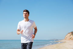 Concentrated young sportsman running on the beach Stock Images