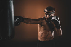 Concentrated young sportsman training thai boxing with punching bag Royalty Free Stock Photo