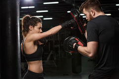 Concentrated young strong sports lady boxer make exercises. Image of concentrated young strong sports lady boxer make exercises in gym with man trainer and royalty free stock images