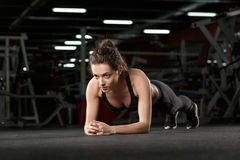 Concentrated young strong sports lady make plank. Picture of concentrated young strong sports lady make plank exercise in gym and looking aside stock photography
