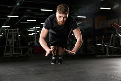 Concentrated young strong sports man make sport exercise. Image of concentrated young strong sports man make sport exercise in gym and looking aside Stock Images