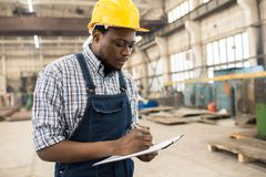Taking Inventory in Modern Plant. Concentrated young technician wearing overall and protective helmet standing at spacious production department of modern plant Stock Image