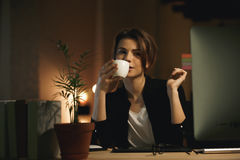 Concentrated young woman designer drinking coffee. Royalty Free Stock Photography
