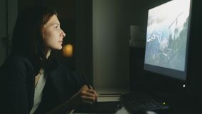 Concentrated young woman designer working in office at night using computer and graphics tablet to finish job