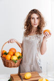 Concentrated young woman holding basket with a lot of citruses Royalty Free Stock Photography