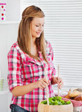 Concentrated young woman preparing a salad stock photos