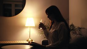 Concentrated young woman reads a book and makes a sip of water out of a glass stock footage