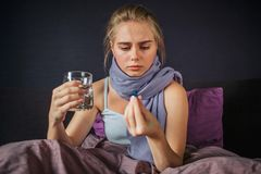 Concentrated young woman sits on bed and looks at medicine she holds with fingers. There is glass of water in another royalty free stock images
