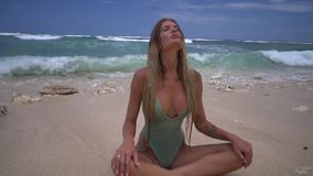 Concentrated young woman sits in lotus position in the ocean waves, the beach with sand, beautiful relaxation and stock video footage