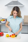 Concentrated young woman standing in kitchen cutting vegetables Royalty Free Stock Photo