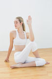 Concentrated young woman stretching her body sitting in sports hall Stock Photos