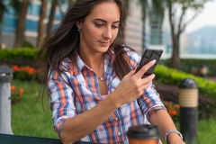 Concentrated young woman typing a text message on her mobile phone outdoors. Serious female using smartphone. Stock Photos
