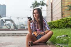 Concentrated young woman typing a text message on her mobile phone outdoors. Serious female using smartphone. stock image