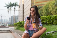Concentrated young woman typing a text message on her mobile phone outdoors. Serious female using smartphone. stock images