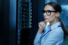 Concentrated young woman working in a data center. Best job. Serious meditative woman working with equipment and thinking royalty free stock image