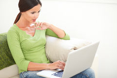 Concentrated young woman working on laptop royalty free stock photos