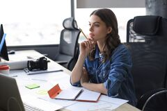 Free Concentrated Young Woman Writing Something Down While Working In The Office Stock Photography - 180624282