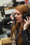Concentrating beautiful singer recording a song Royalty Free Stock Photos