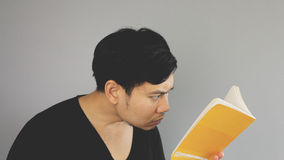 Concentrating on the book. An asian man with black t-shirt royalty free stock photography
