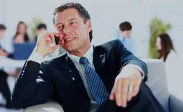 Concentrating businessman on call, coworkers talkling in background . Concentrating businessman on call, coworkers talkling in background Royalty Free Stock Image