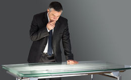 Concentrating businessman leaning on desk Royalty Free Stock Image