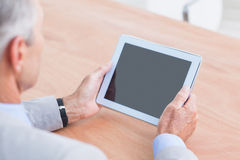 Concentrating businessman using a tablet Stock Photos