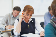Concentrating female mature woman sitting in classroom Royalty Free Stock Photo