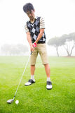 Concentrating golfer lining up his shot. At the golf course Royalty Free Stock Images
