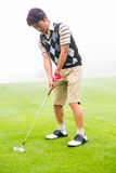 Concentrating golfer lining up his shot. At the golf course Royalty Free Stock Image