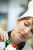 Concentrating head chef putting mint leaf on little cake Stock Photo
