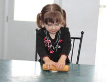 Concentrating on Making a Tortilla. Young toddler girl concentrating on rolling out a tortilla Stock Photo