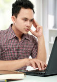 Concentrating man working with laptop at his desk Stock Photography
