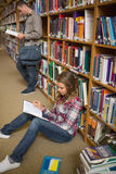Concentrating student reading book on library floor Stock Photography