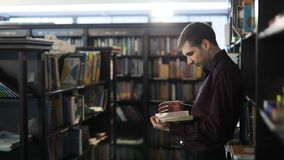 Student reading a book in the library. Concept: educational, portrait, library, and studious, relax. Concentrating student studying in the library in college stock footage