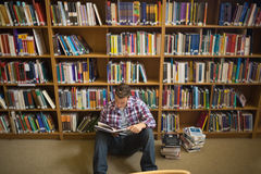 Concentrating young student sitting on library floor reading Stock Photography