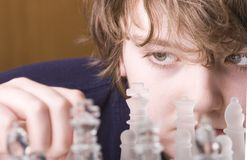 Concentration. Young boy concentrating while playing a game of chess royalty free stock image