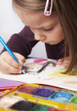 Concentration. Child concentrated on drawing a picture stock photography
