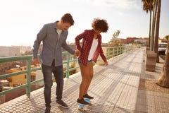 Concentration de jeunes couples apprenant à faire de la planche à roulettes Photos libres de droits
