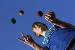 Concentration, juggling balls. Pupil is juggling with five balls. Success in school with concentration royalty free stock photography