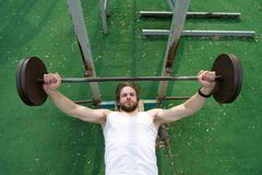 Concentrato sull'esercizio Addestramento dell'atleta dell'uomo con il bilanciere L'uomo atletico spinge verso l'alto il bilancier Fotografia Stock Libera da Diritti