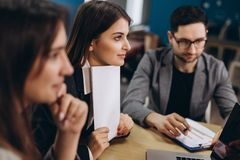 Concentrazione completa sul lavoro Gruppo di gente di affari che lavora e che comunica mentre sedendosi alla scrivania insieme fotografie stock