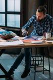 Concentrazione della pittura dell'uomo del materiale illustrativo dello studio dell'artista immagine stock