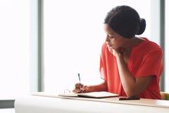 Concentrazione della scrittura femminile afroamericana giovane dell'imprenditore in suo taccuino Fotografie Stock