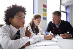 Concentrazione dello studente maschio Wearing Uniform Working della High School alla Tabella con l'insegnante Talking To Pupils n fotografie stock