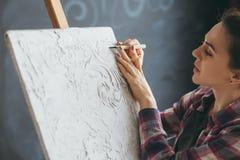 Concentrazione nello strumento della donna del materiale illustrativo di sollievo dell'artista fotografia stock