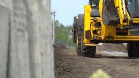 Concentreer van concrete plakken opnieuw waarop een gele bouwtractor die op een landweg berijdt stock video