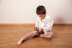 Concentreerde weinig jongen die met smartphone spelen royalty-vrije stock afbeelding